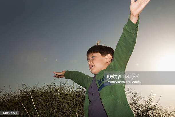 Boy playing outdoors with arms raised in air