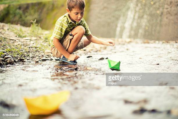 Junge spielt Papier-Boote auf dem Fluss