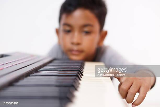 boy playing piano against white background - heri mardinal stock pictures, royalty-free photos & images