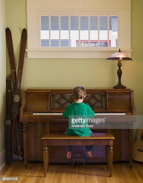 boy playing piano at home
