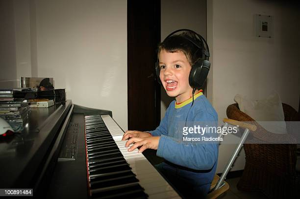 boy playing piano - radicella stock photos and pictures