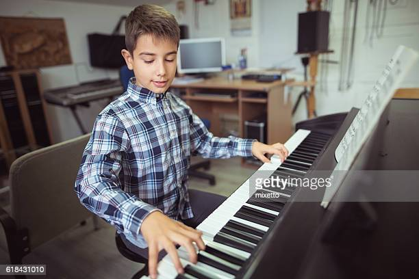 boy playing piano - pianist stock photos and pictures