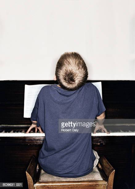Boy (10-12) playing piano, rear view