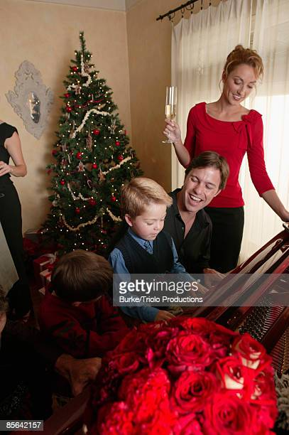 Boy playing piano with family
