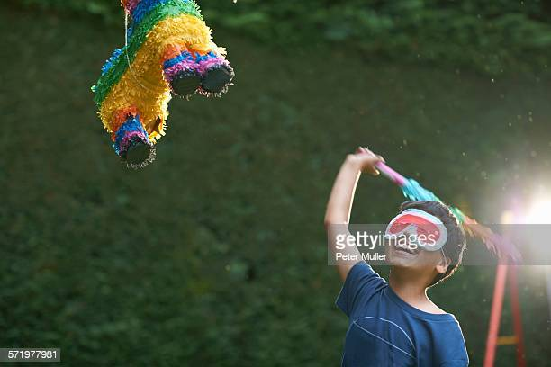 boy playing pinata in garden - pinata stock pictures, royalty-free photos & images