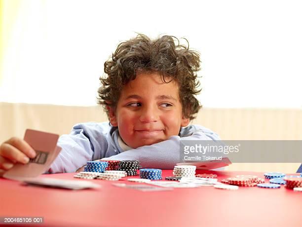 Boy (8-10) playing poker, smiling, close-up