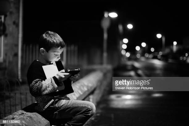 Boy Playing Portable Games Console in Street