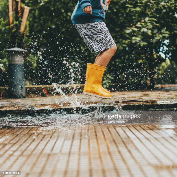 boy playing puddles - rain stockfoto's en -beelden