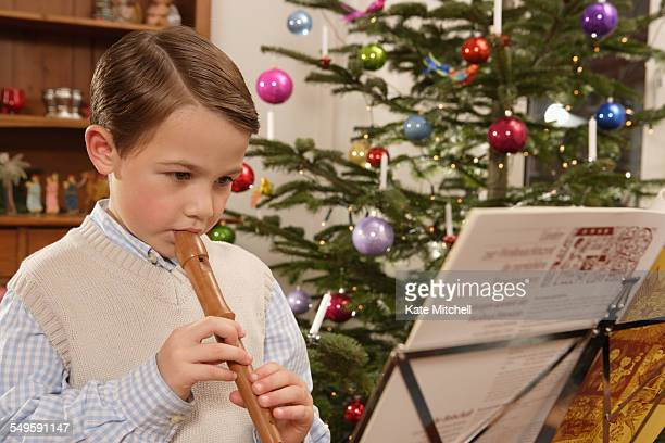 Boy Playing Recorder by Christmas Tree