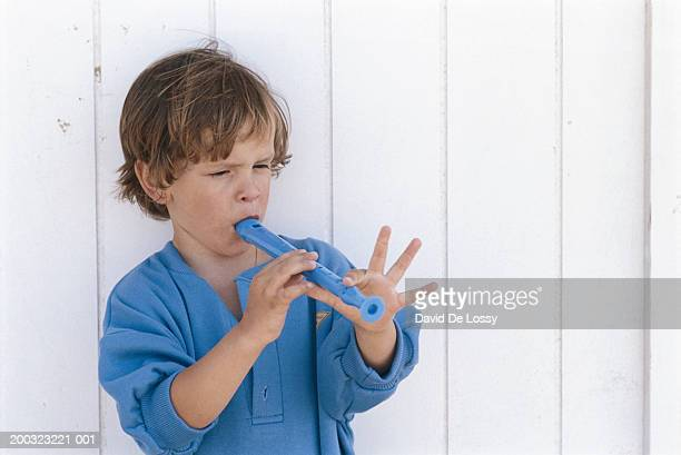 Boy (4-5) playing recorder