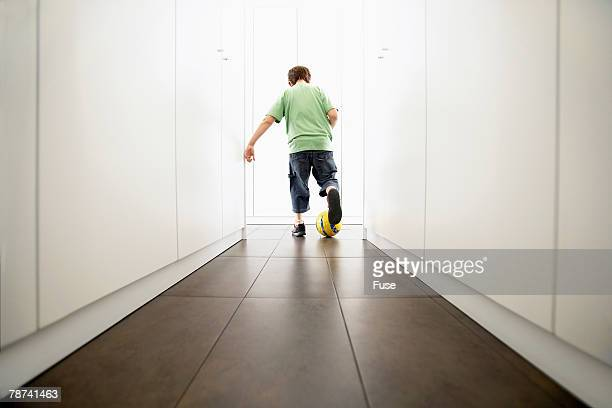Boy Playing Soccer in the Hallway
