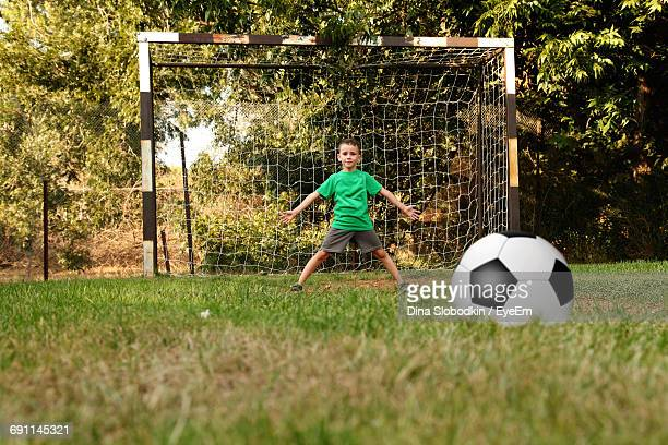 boy playing soccer on field - focus on background stock pictures, royalty-free photos & images