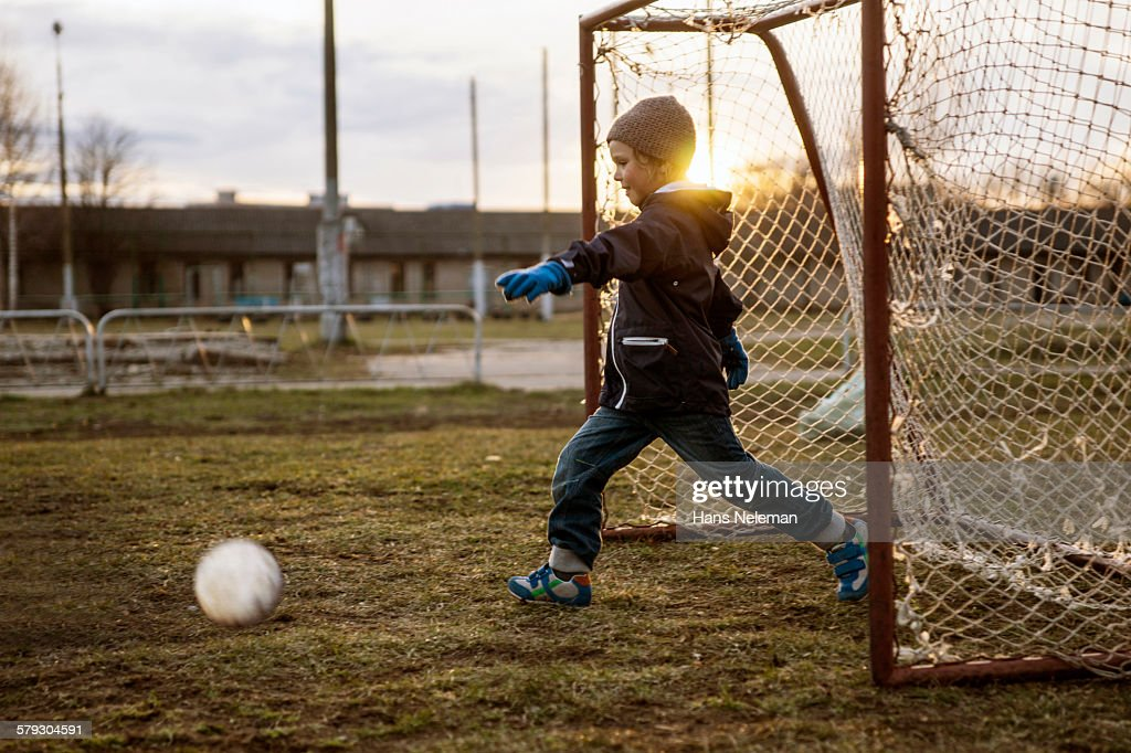 Boy playing soccer outdoors : Stock Photo