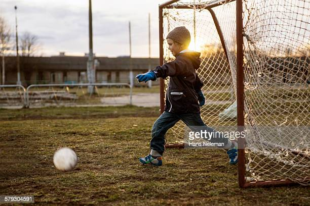 Boy playing soccer outdoors