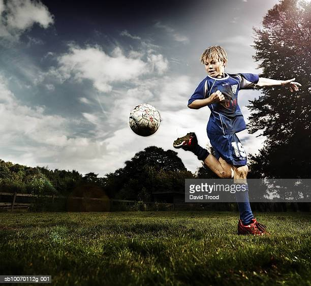Boy (10-11) playing soccer