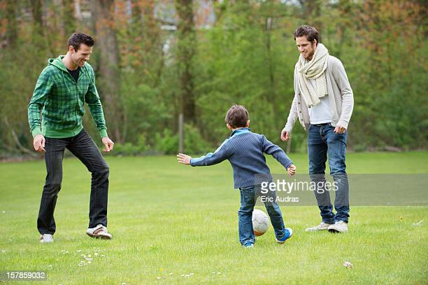 boy playing soccer with two men in a park - chutar - fotografias e filmes do acervo