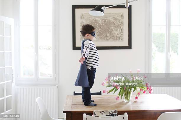 A boy playing superhero in the kitchen