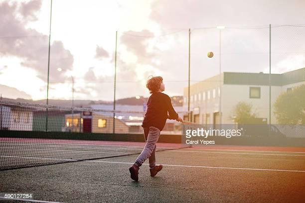 Boy playing tennis  in sunset