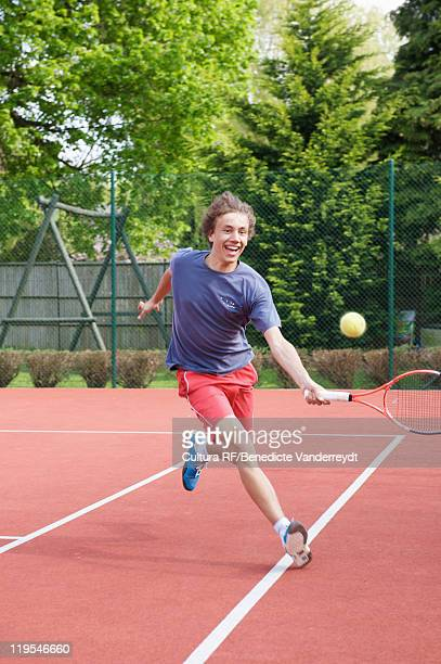 boy playing tennis on court - tennis racquet stock pictures, royalty-free photos & images
