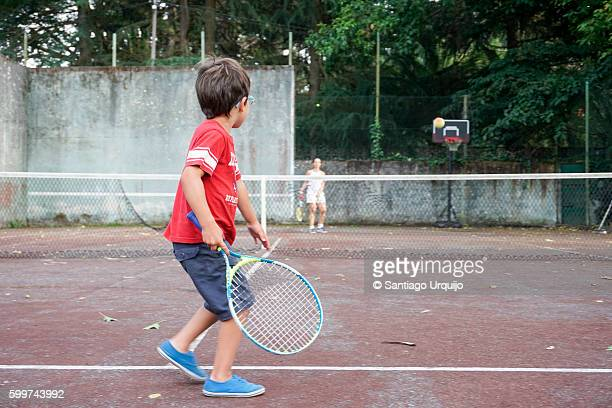 Boy playing tennis with his mother