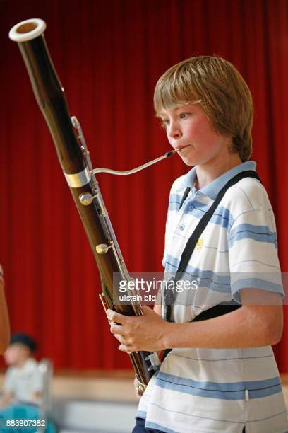 boy playing the bassoon / boys / child / children / childhood / musical instrument