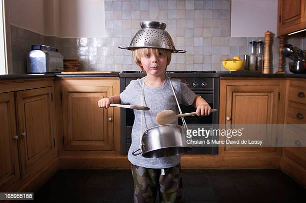 boy playing the drums on a pan with spatulas - musical instrument stock pictures, royalty-free photos & images