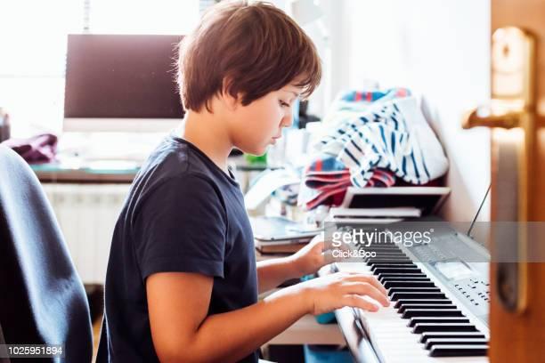 boy playing the piano (nine years old) in a domestic room - 8 9 years stock pictures, royalty-free photos & images
