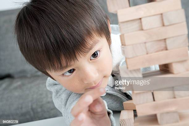Boy playing tower of wooden blocks, close up