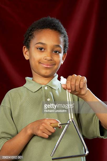 boy (7-9) playing triangle, smiling, portrait - triangle percussion instrument stock photos and pictures