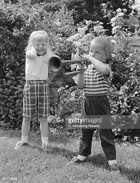 Boy playing trumpet in backyard, girl grimacing, holding hands over her ears.