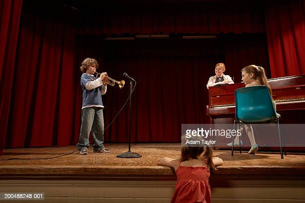 boy (10-12) playing trumpet on stage, watched by teacher and two girls - ensayo espectáculo fotografías e imágenes de stock