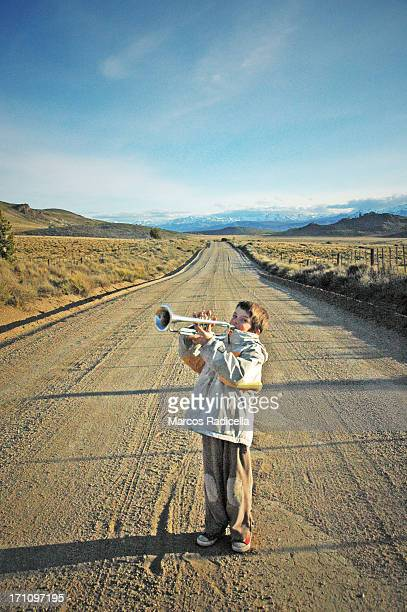 boy playing trumpet on the road - radicella stock pictures, royalty-free photos & images