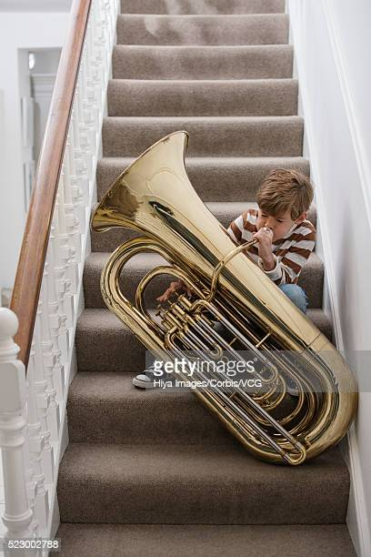 Boy playing tuba on stairs