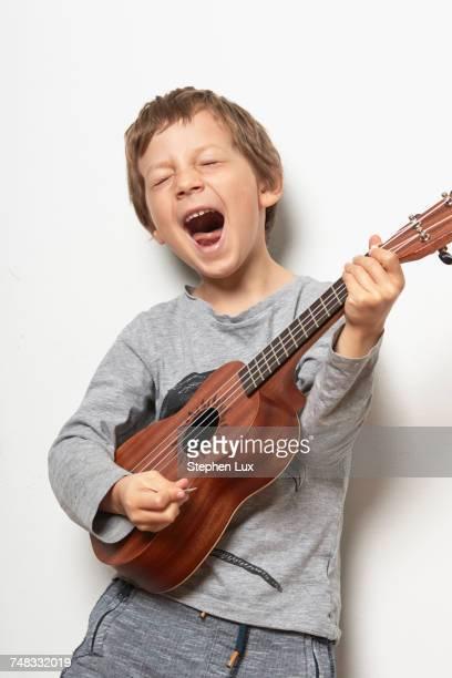 boy playing ukulele, pulling face - ukulele stock-fotos und bilder
