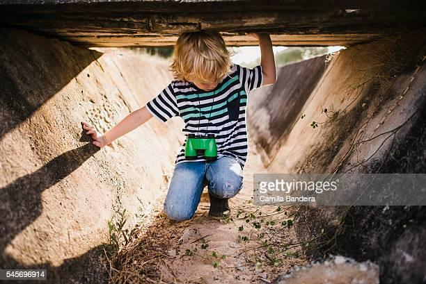 Boy playing under ditch