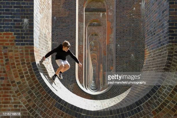 boy playing underneath viaduct - viaduct stock pictures, royalty-free photos & images