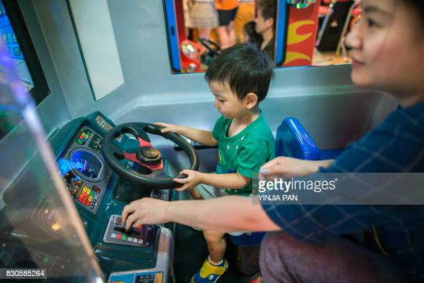 Boy playing video game at video arcade with his mother
