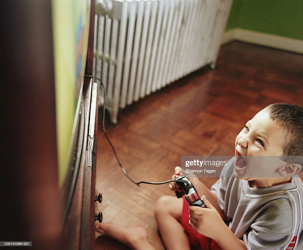 Boy (5-7) playing video game on television, elevated view : Stock Photo