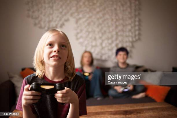 Boy playing video game with friends at home