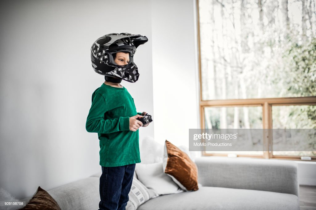 Boy playing video games and wearing motorcycle helmet : Stock Photo