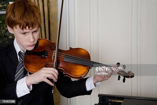 Boy (12-13) playing violin, close-up