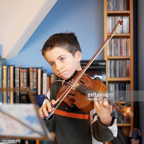 Boy (8-10) playing violin, mid section, close-up (focus on boy's face)