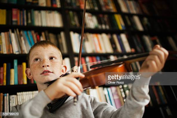 boy (10-12) playing violin - violin stock pictures, royalty-free photos & images