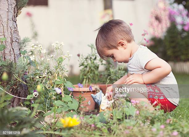 boy playing with a gnome in the garden - gnome stock pictures, royalty-free photos & images