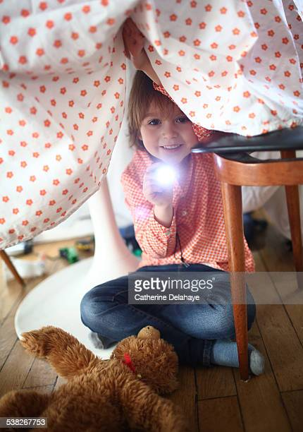 A boy playing with a lamp under a kitchen table