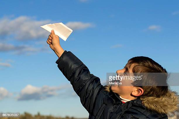 Boy playing with a paper airplane