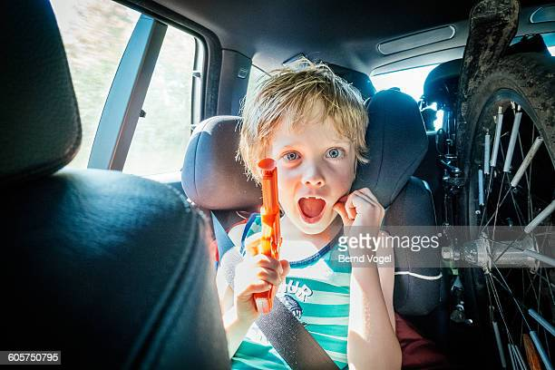 boy playing with a toy gun in a car