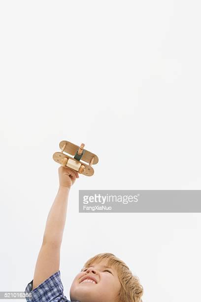 jungen spielen mit einem spielzeug-flugzeug - doppeldecker flugzeug stock-fotos und bilder