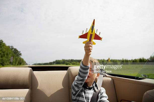 Boy (6-7) playing with airplane in back of convertible