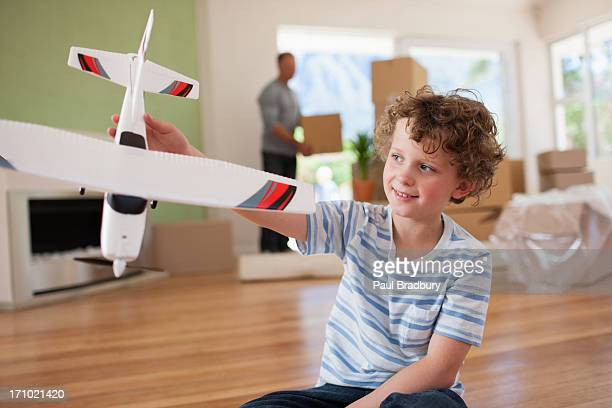 Boy playing with airplane in new home